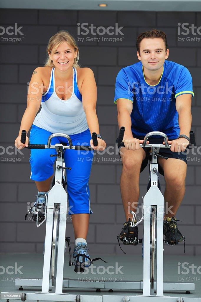 Man and woman spinning on bicycles in a gym. royalty free stockfoto