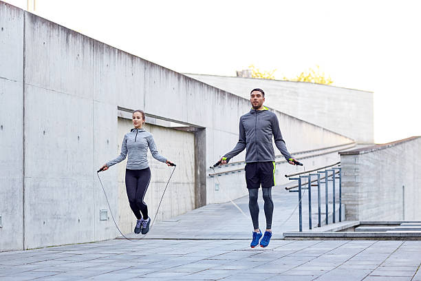 man and woman exercising with jump-rope outdoors stock photo