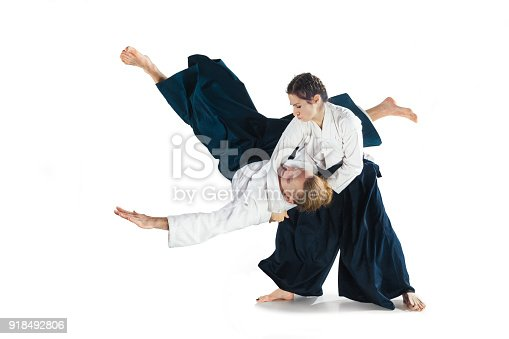 Man and woman fighting at Aikido training in martial arts school. Healthy lifestyle and sports concept. Man with beard in white kimono on white background. Karate woman with concentrated face in uniform. Isolated on white studio background