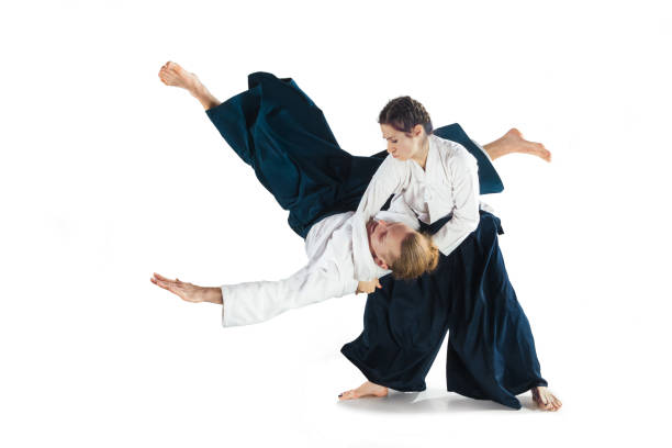 Man and woman fighting at Aikido training in martial arts school stock photo