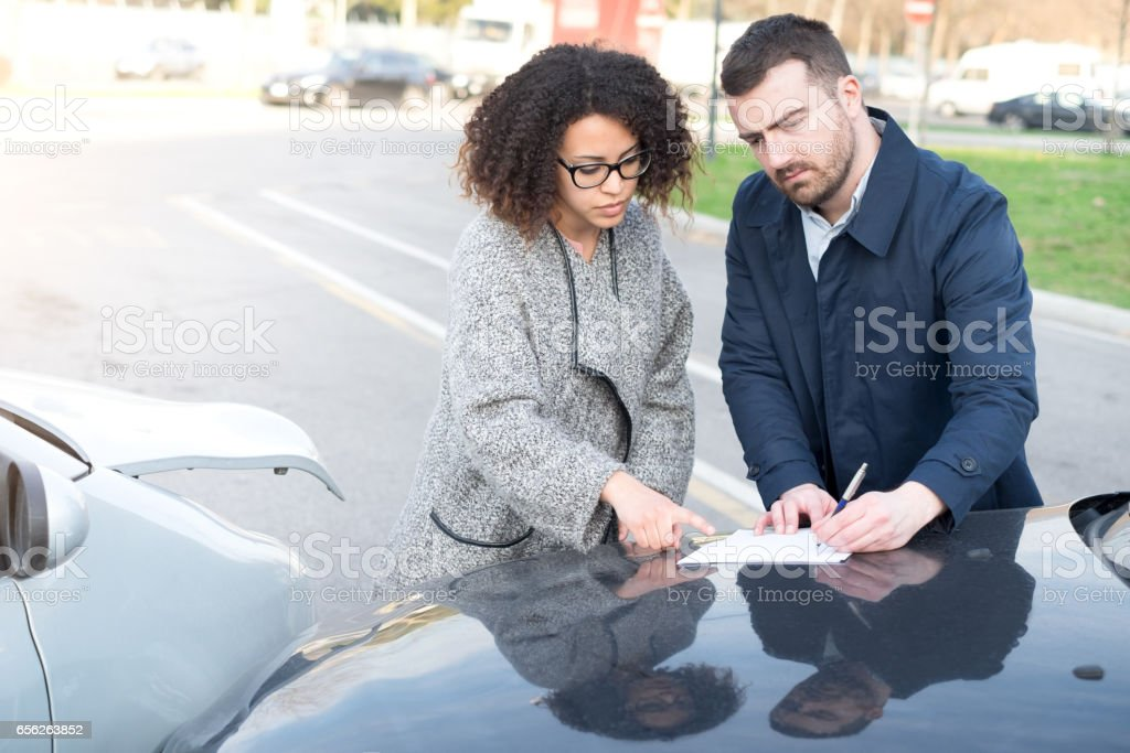 Man and woman filling an insurance car form stock photo