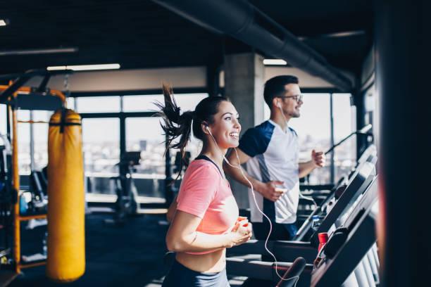 man en vrouw fitness gym draait op loopband - healthclub stockfoto's en -beelden