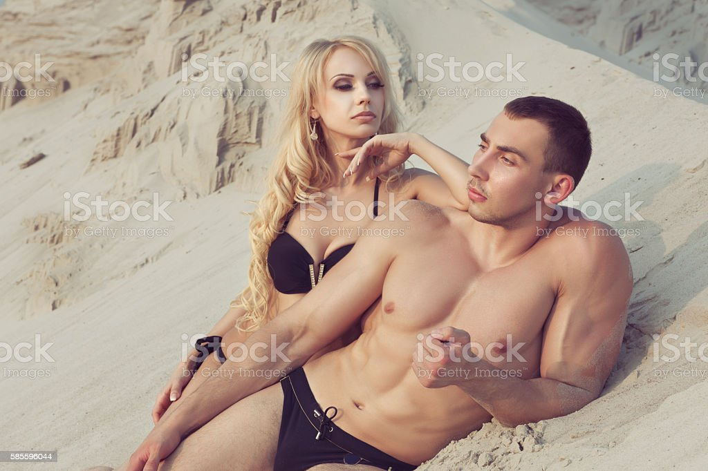 Man and woman flirting on the sand. stock photo