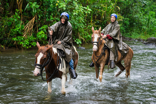 Man and woman galloping in River Arenal during Horseback riding on foot of  Volcano Arenal, Costa Rica.