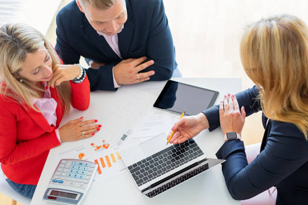 Man and woman getting help from professional financial consultant stock photo