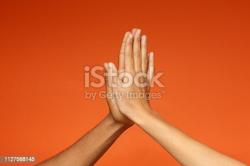 African-american man and woman greeting each other with high five, clapping hands on orange background