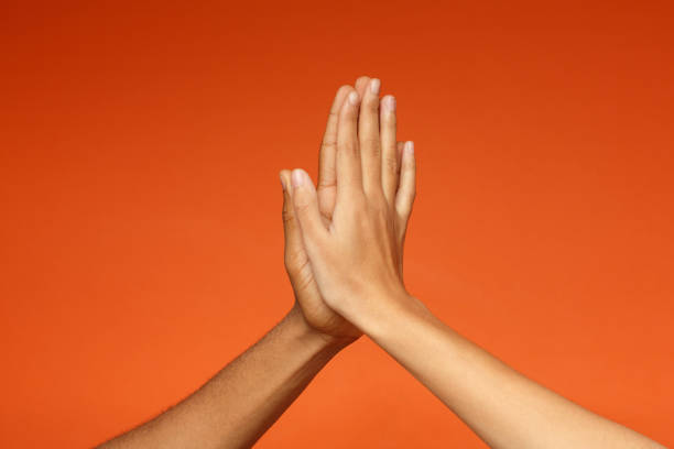 Man and woman greeting each other with high five stock photo