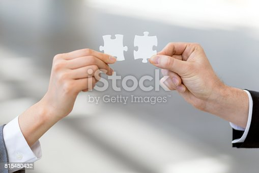 istock man and woman hand holding jigsaw puzzles, business matching concept 815480432