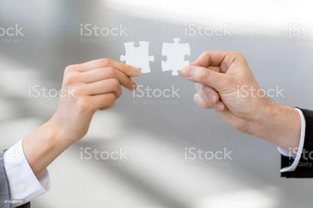 man och kvinna hand som håller pussel, matchande affärsidé bildbanksfoto