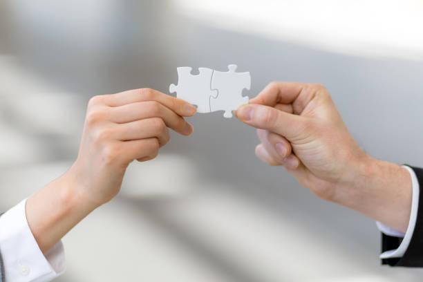 hombre y mujer mano rompecabezas, concepto que empareja - cosas que van juntas fotografías e imágenes de stock
