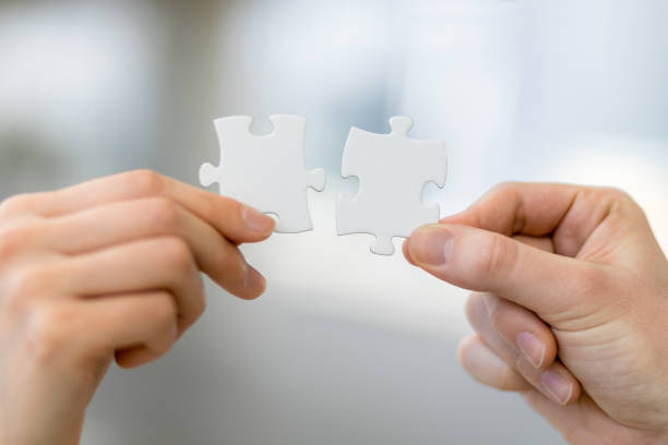 man and woman hand holding jigsaw puzzles, business matching concept - foto stock