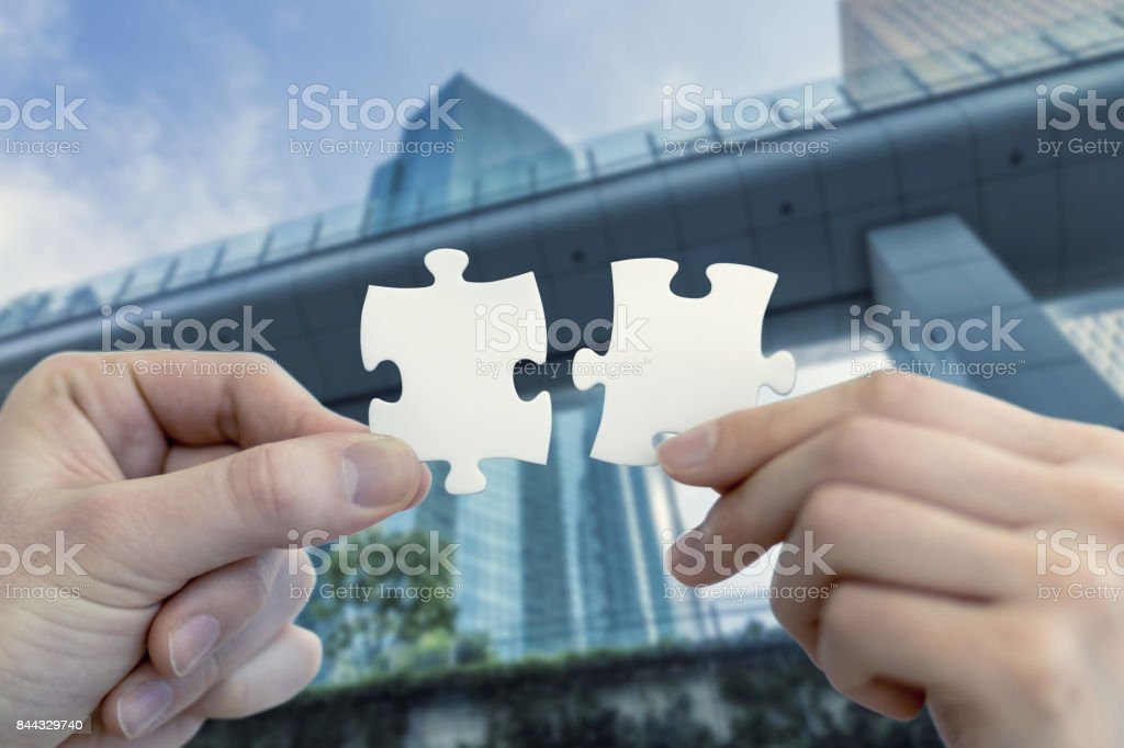 man and woman hand holding jigsaw puzzles, business matching concept stock photo