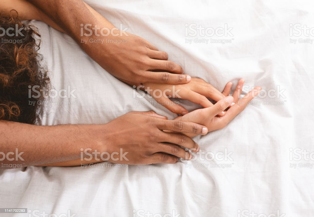 Man and woman hands having sex on bed - Foto stock royalty-free di Adulto