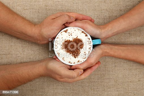 Close up man and woman hands hold and hug together big full cup of latte cappuccino coffee with heart shaped chocolate on milk froth over canvas tablecloth, elevated top view, directly above