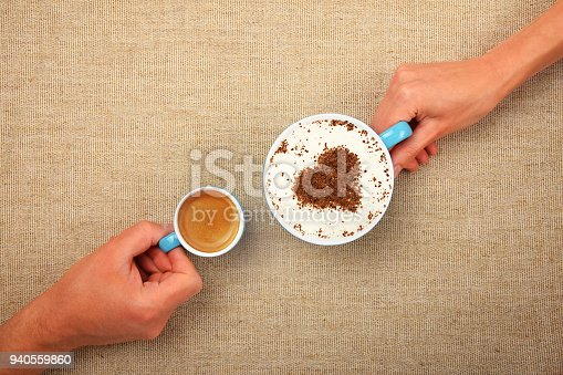Close up man and woman hands hold small espresso and big full cup of latte cappuccino coffee with heart shaped chocolate on milk froth over canvas tablecloth, elevated top view, directly above