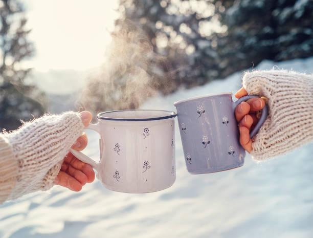 adam ve kadın el mittens kış orman glade üzerinde sıcak çay bardağı ile örgü - glühwein stok fotoğraflar ve resimler