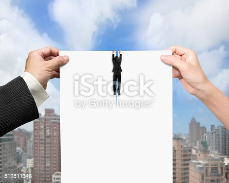 656916072istockphoto Man and woman hands tearing blank paper with businessman hanging 512511346