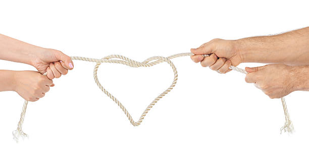 Man and woman hands with heart shaped rope stock photo