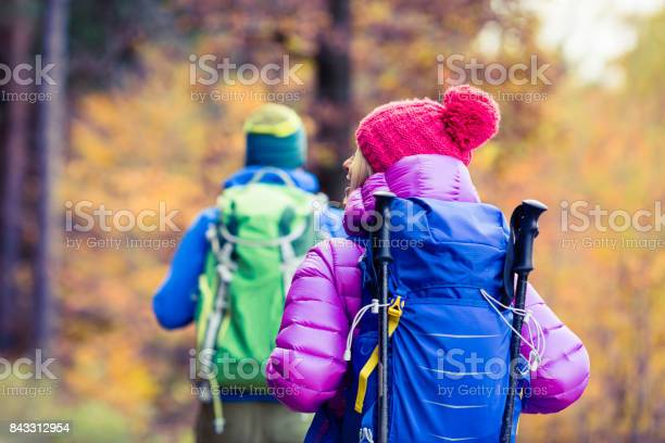 Photo of Man and woman happy couple hikers walking in autumn woods
