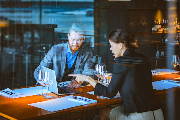 Man and Woman Having a Discussion During Lunch Time in a High-End Restaurant stock photo