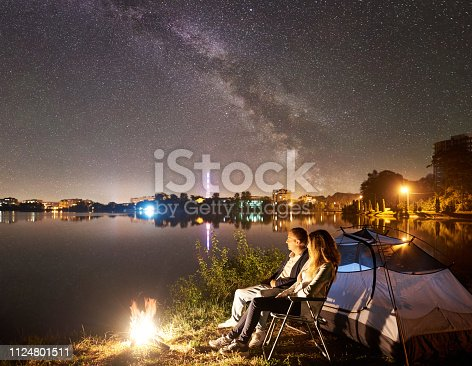 678554980 istock photo Man and woman having a rest on shore under night sky 1124801511
