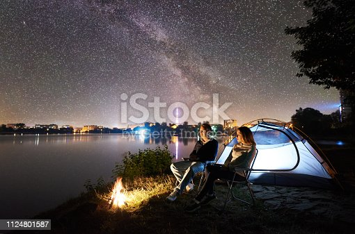 678554980istockphoto Man and woman having a rest on shore under night sky 1124801587