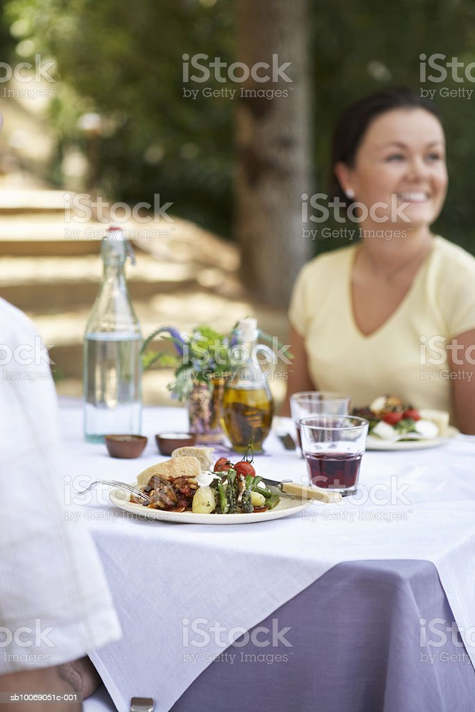 Man and woman having dinner outdoor party, focus on food on table foto de stock royalty-free