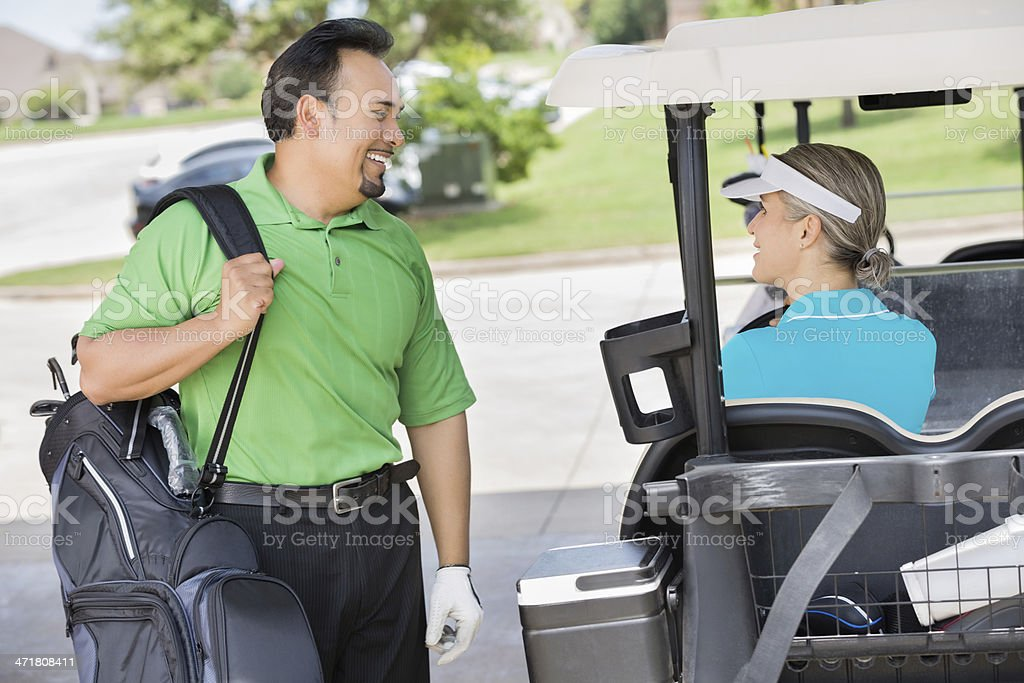 Man and woman having friendly conversation before playing golf royalty-free stock photo