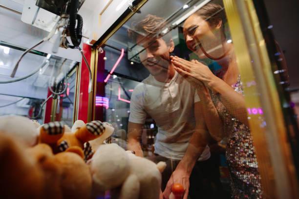 mann und frau, die spaß an einem spiele-arcade - arkade stock-fotos und bilder