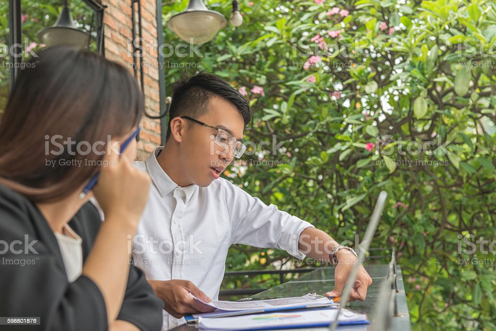 Man and woman having team discussion at outdoor space stock photo