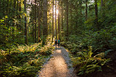 Mature father and teenaged daughter hiking through forest on Mt. Seymour Provincial Park, North Vancouver, British Columbia, Canada\n\n
