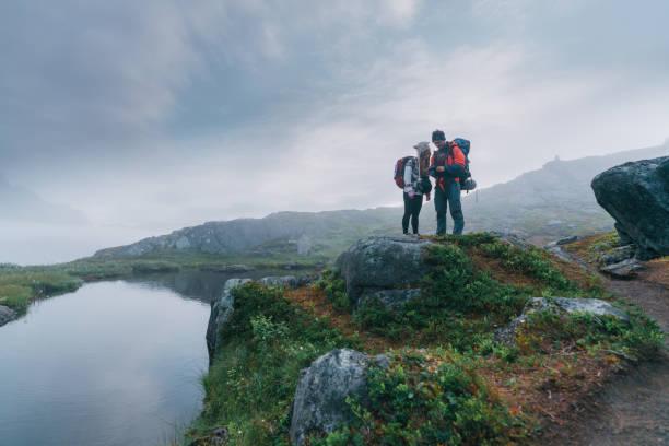 Man and woman hiking in mountain on Senja island stock photo