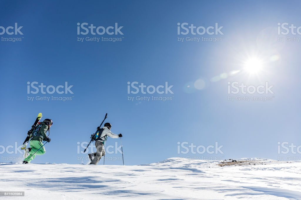Man and woman hiking up a mountain carrying skis for backcountry skiing stock photo