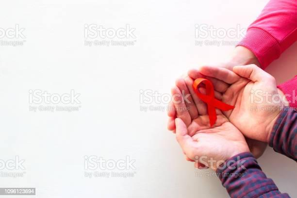 Man And Woman Hold Red Ribbon - zdjęcia stockowe i więcej obrazów AIDS