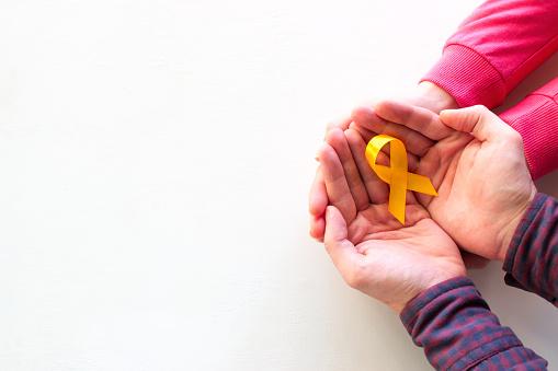man and woman hold yellow ribbon