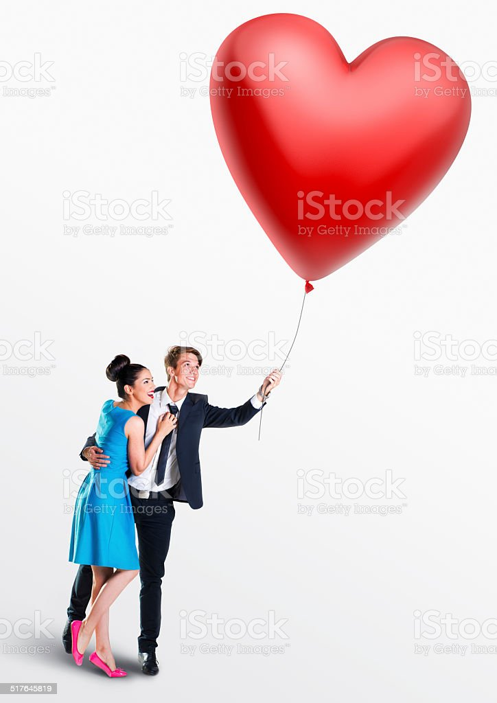 Man and woman holding a heart- shaped balloon stock photo