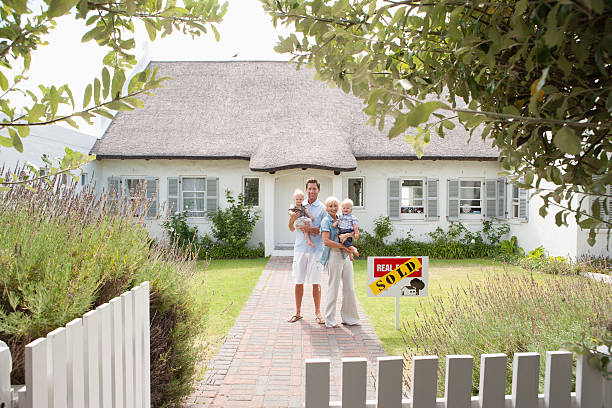 Man and woman holding babies in front of house with sold sign and white fence stock photo