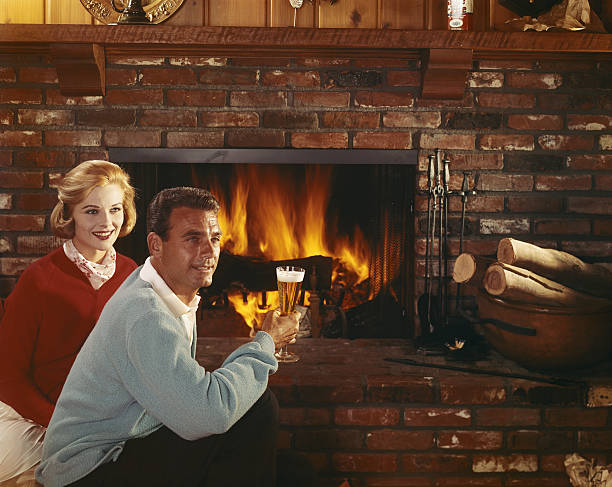 Man and woman holding glass near fireplace and looking away stock photo