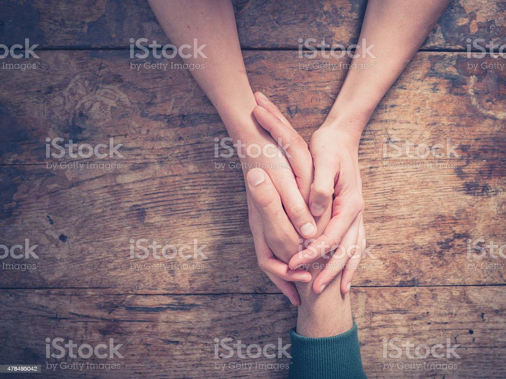 Man and woman holding hands at a table
