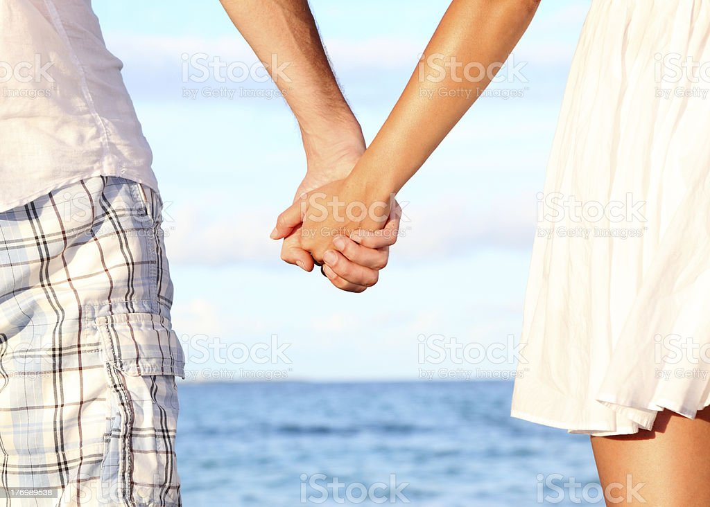 Man and woman holding hands at the seaside stock photo