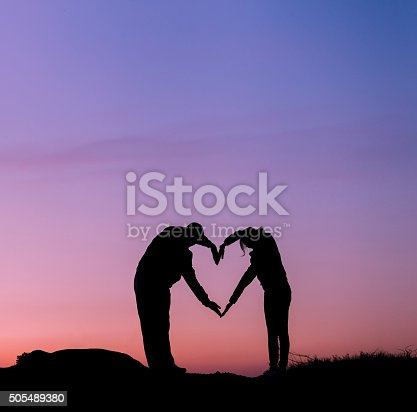 536952169 istock photo Man and woman holding hands in heart shape at sunset 505489380