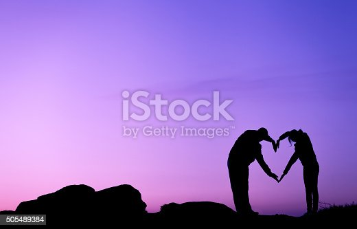 536952169 istock photo Man and woman holding hands in heart shape at sunset 505489384