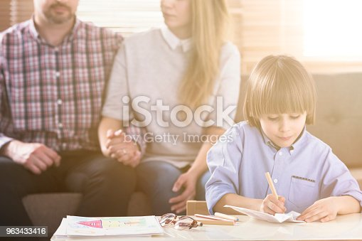 istock Man and woman holding hands on a couch and a boy in front drawing pictures by a table during a family psychotherapy session. Front view. Flare. Blurred background. 963433416