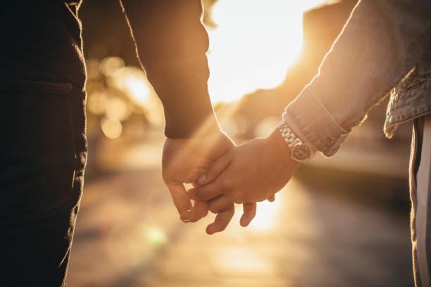 homme et femme tenant par la main - se tenir par la main photos et images de collection