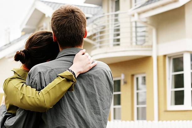 Man and woman hugging in front of a house stock photo