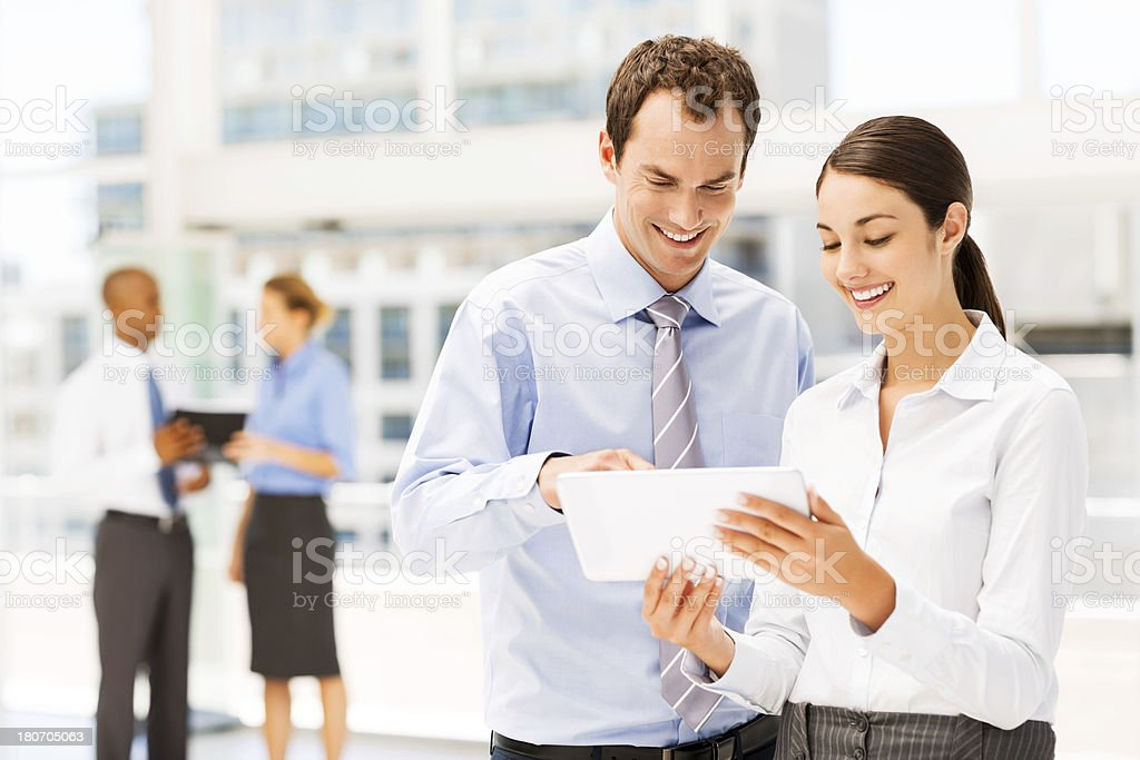 Man and woman in a business setting using a digital tablet royalty-free stock photo