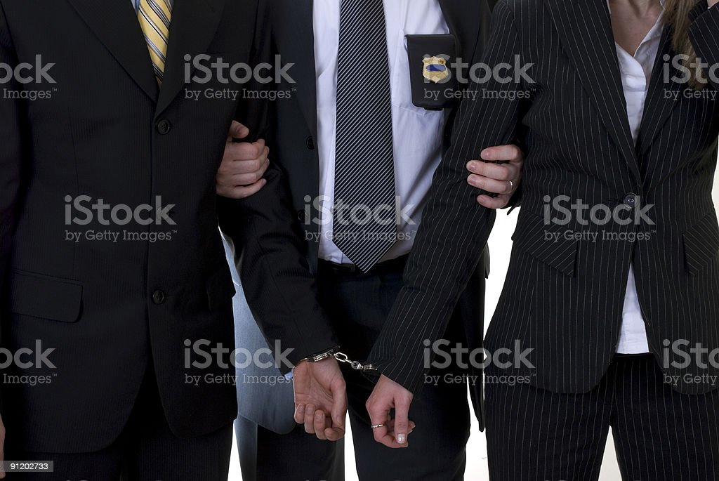 Man and woman in a business suit handcuffed by police royalty-free stock photo