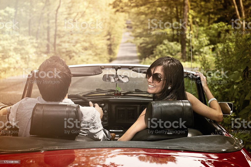 Man and woman in a red convertible on forest road royalty-free stock photo