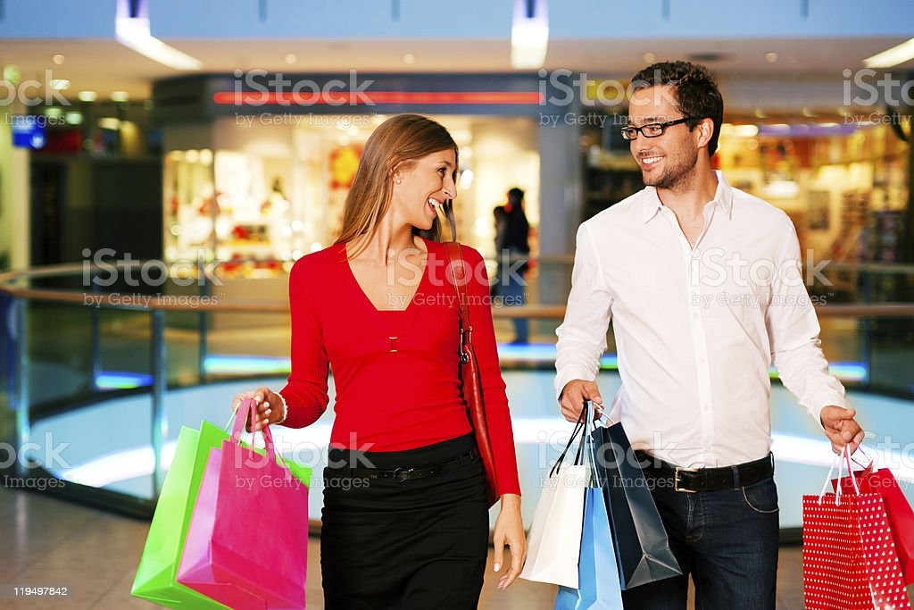 Man and woman in a shopping mall carrying bags Couple - man and woman - in a shopping mall with colorful bags simply having fun Adult Stock Photo