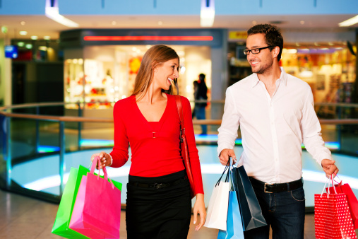 Man And Woman In A Shopping Mall Carrying Bags Stock Photo - Download Image Now